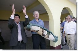President George W. Bush holds a gift from Mayor Raymundo Juarez during a visit Monday, March 12, 2007, to Santa Cruz Balanya, Guatemala. Pictured at right is Guatemalan President Oscar Berger.  White House photo by Eric Draper