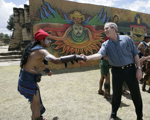 President George W. Bush reaches out to thank a performer Monday, March 12, 2007, after a demonstration of a Mayan Ritual competition at Iximche, Guatemala. White House photo by Eric Draper
