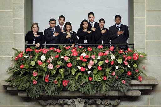 Staff members stand for the playing of the national anthems Monday, March 12, 2007, during the arrival ceremony at the Palacio Nacional de la Cultura in Guatemala City, marking the visit of President George W. Bush and Mrs. Laura Bush to the country. White House photo by Paul Morse