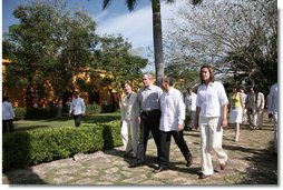 President George W. Bush and Mrs. Laura Bush walk with President Felipe Calderon and Mrs. Margarita Zavala to the arrival ceremonies Tuesday, March 13, 2007, in Temozon Sur, Mexico. The President and Mrs. Bush are on the final leg of their five-country, Latin American visit, and are scheduled to return to Washington Wednesday.  White House photo by Paul Morse