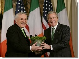 President George W. Bush is presented with a bowl of shamrocks by Ireland's Prime Minister Bertie Ahern at a ceremony in the Roosevelt Room at the White House, March 16, 2007. White House photo by Joyce Boghosian
