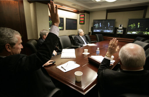 President George W. Bush and Vice President Dick Cheney wave from the Situation Room of the White House Monday, March 19, 2007, as they're joined in a video teleconference by Prime Minister Nouri al-Maliki of Iraq. White House photo by Eric Draper