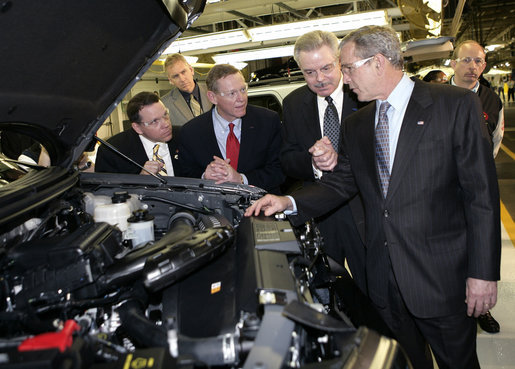 President George W. Bush takes a look under a hood during his tour Tuesday, March 20, 2007, of the Ford Motor Company - Kansas City Assembly Plant in Claycomo, Missouri, joined by, from left, U.S. Rep. Sam Graves, Ford President and CEO Alan Mulally and Ford Group Vice President Derrick Kuzak. White House photo by Eric Draper