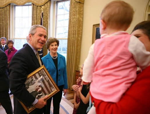 President George W. Bush and Mrs. Laura Bush greet the family members of former President Lyndon Baines Johnson in the Oval Office, Friday, March 23, 2007, for the signing of H.R. 584 designating the U.S. Department of Education in Washington, D.C., as the Lyndon Baines Johnson Federal Building. President Bush holds an old photo of President Johnson and Lady Bird Johnson to show members of the Johnson family. White House photo by Eric Draper