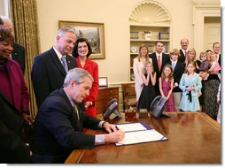 President George W. Bush, joined by the family of former President Lyndon Baines Johnson, signs H.R. 584 designating the U.S. Department of Education in Washington, D.C., as the Lyndon Baines Johnson Federal Building, Friday, March 23, 2007 in the Oval Office. White House photo by Eric Draper
