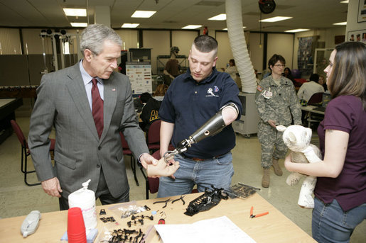 President George W. Bush talks with U.S. Army Sgt. Dennis Cline II of Memphis, Tenn., about therapy Friday, March 30, 2007, during a visit to Walter Reed Army Medical Center in Washington, D.C. Also pictured is Sgt. Cline's wife Brooke Ann Cline. White House photo by Eric Draper