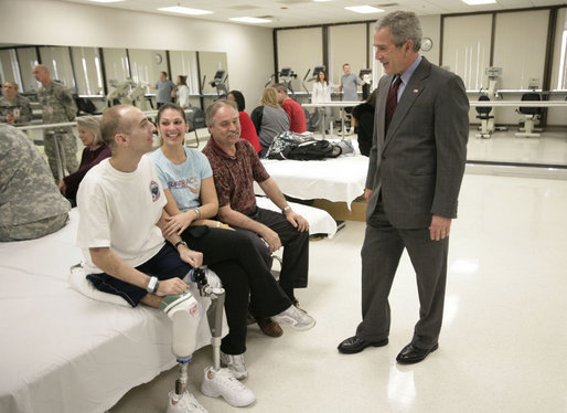 President George W. Bush spends time with Minnesota National Guard Sgt. John Matthew Kriesel of Cottage Grove, Minn., Friday, March 30, 2007, during a visit to Walter Reed Army Medical Center in Washington, D.C. Sitting with Sgt. Kriesel is his wife, Katharine Marie Kriesel, and father John Joseph Kriesel. White House photo by Eric Draper