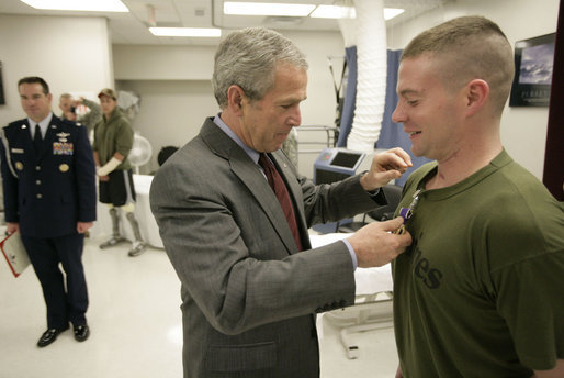 President George W. Bush presents the Purple Heart to U.S. Marine Lance Cpl. Joshua Ryan Bleill of Greenfield, Ind., during a visit Friday, March 30, 2007, to the Walter Reed Army Medical Center in Washington, D.C. Bleill is recovering from injuries sustained in Operation Iraqi Freedom. White House photo by Eric Draper
