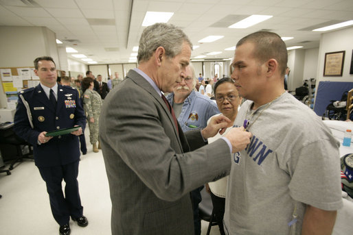 President George W. Bush presents the Purple Heart to U.S. Army Private First Class Casimir Domingo Werda of Novi, Mich., during a visit Friday, March 30, 2007, to the Walter Reed Army Medical Center in Washington, D.C. Werda is recovering from injuries sustained in Operation Iraqi Freedom. Werda's parents Floserfina Demano Werda and Gregory Lee Werda are seen background. White House photo by Eric Draper