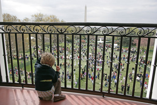 A young guest from the breakfast reception for the 2007 White House Easter Egg Roll peeks through the railing on the Truman Balcony for a birds-eye view of the activities on the South Lawn. White House photo by Shealah Craighead
