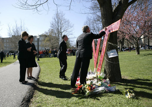 President George W. Bush signs a large Virginia Tech emblem, as the President and Mrs. Laura Bush stop to pay their respects at a campus memorial following the Convocation Tuesday, April 17, 2007 in Blacksburg, Va., honoring the shooting victims at Virginia Tech. The Bushes are accompanied by Governor Tim Kaine and his wife, Anne Holton. White House photo by Eric Draper