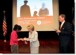 "Mrs. Lynne Cheney hands out a copy of, ""The Citizen's Almanac,"" during a special naturalization ceremony at the National Archives Tuesday, April 17, 2007, in Washington, D.C."