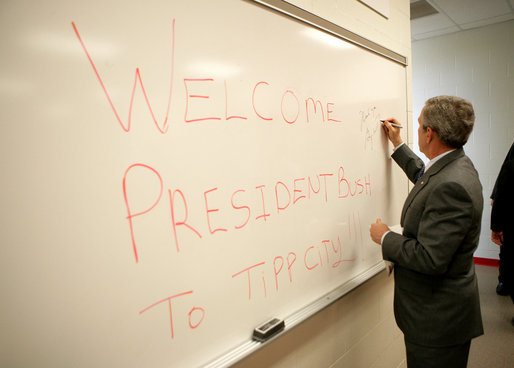 President George W. Bush signs a dry erase board with a permanent marker as he passes through a locker room during his visit to Tipp City High School in Tipp City, Ohio, Thursday, April 19, 2007. White House photo by Eric Draper