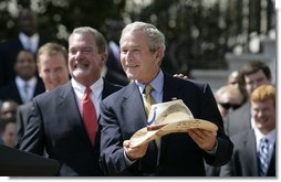 President George W. Bush shows the signatured cowboy hat presented to him by Indianapolis Colts team owner and CEO Jim Irsay, left, during the White House ceremony to honor the Super Bowl champions Monday, April 23, 2007. White House photo by Eric Draper