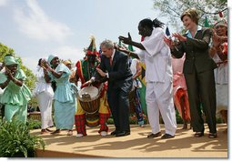 President George W. Bush and Mrs. Laura Bush take the stage with the Kankouran West African Dance Company after delivering remarks during a ceremony marking Malaria Awareness Day Wednesday, April 25, 2007, in the Rose Garden.  White House photo by Eric Draper