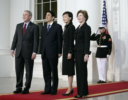 President George W. Bush and Mrs. Laura Bush stand for press photographs with Japanese Prime Minister Shinzo Abe and his wife Mrs. Akie Abe Thursday, April 26, 2007, as they arrive at the North Portico for a social dinner at the White House. White House photo by Eric Draper
