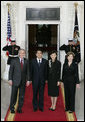 President George W. Bush and Mrs. Laura Bush stand for press photographs with Japanese Prime Minister Shinzo Abe and his wife Mrs. Akie Abe Thursday, April 26, 2007, as they arrive at the North Portico for a social dinner at the White House. White House photo by Shealah Craighead