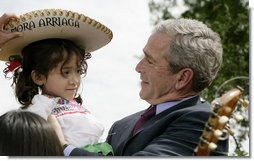 President George W. Bush embraces Angelica Mora Arriaga, a member of the Los Hermanos Mora Arriaga mariachi band, in the Rose Garden at the White House Friday, May 4, 2007, to celebrate Cinco de Mayo. White House photo by Eric Draper