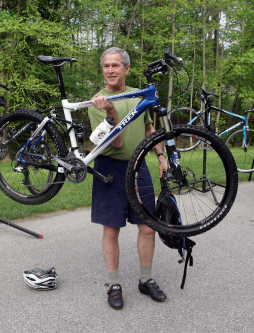 "President George W. Bush holds up his mountain bike before riding with members of the President's Council on Physical Fitness and Sports Saturday, May 5, 2007, in Beltsville, Md. ""It doesn't take much time to stay fit -- 30 minutes five days a week; 30 minutes of walking, 30 minutes of running, 30 minutes of biking, 30 minutes of swimming on a regular basis will help deal with a lot of health issues here in America,"" said President Bush, who exercises regularly. White House photo by Joyce Boghosian"