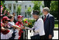 President George W. Bush and Her Majesty Queen Elizabeth II of Great Britain stop to meet a group of children offering flowers Monday, May 7, 2007, during their walk from the White House to Blair House, where the Queen Elizabeth II and His Royal Highness the Prince Philip, Duke of Edinburgh, are staying during their visit to Washington, D.C. White House photo by Eric Draper