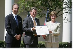 Mrs. Laura Bush presents a plaque to John McLaughlin, center, president and CEO of the USS Midway Museum in San Diego, Calif., and Scott McGaugh, marketing director of the museum, honoring them with a 2007 Preserve America Presidential Award in the Rose Garden at the White House Wednesday, May 9, 2007.  White House photo by Joyce Boghosian