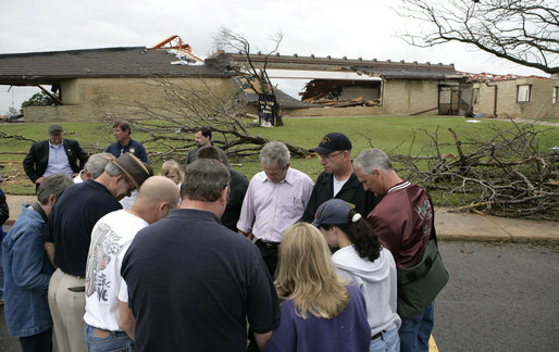 President George W. Bush joins townspeople in prayer Wednesday, May 9, 2007, as he toured a neighborhood in the tornado-ravaged community of Greensburg, Kansas. At least 10 people died in the Friday night storm that destroyed nearly 95 percent of the town. White House photo by Eric Draper