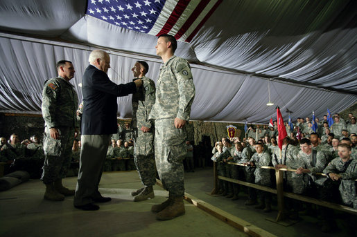 Vice President Dick Cheney awards SSgt Vincent Lewis with the Combat Infantry Badge during a rally for the troops Thursday, May 10, 2007 at Contingency Operating Base Speicher, Iraq. White House photo by David Bohrer