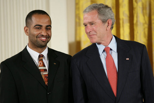 President George W. Bush speaks with award recipient Adeel Khan of Springfield, Va., student body president at Virginia Tech, on stage in the East Room of the White House, where Khan received the President's Volunteer Service Award Thursday, May 10, 2007, in celebration of Asian Pacific American Heritage Month. White House photo by Eric Draper
