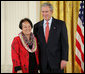 President George W. Bush welcomes Linda Uehara of Mililani, Hawaii, to the stage in the East Room of the White House, to receive the President's Volunteer Service Award Thursday, May 10, 2007, in celebration of Asian Pacific American Heritage Month. White House photo by Eric Draper
