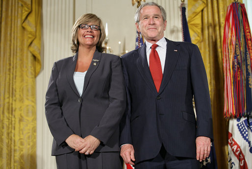 President George W. Bush joins military spouse Cindy Bjerke of Spanaway, Wash., on stage in the East Room of the White House, to receive the President's Volunteer Service Award Friday, May 11, 2007, during a commemoration of Military Spouse Day. White House photo by Eric Draper