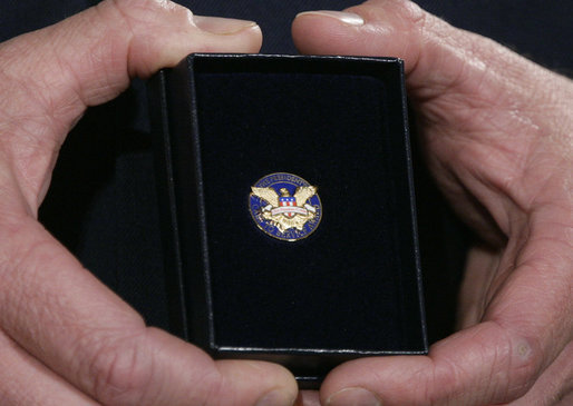 A White House military aide holds the President's Volunteer Service Award medal presented by President George W. Bush to military spouses Friday, May 11, 2007 at the White House, in honor of their outstanding volunteer service and to commemorate Military Spouse Day. White House photo by Eric Draper