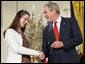 President George W. Bush congratulates military spouse Linda Port of Langley Air Force Base, Va., as she is presented with the President's Volunteer Service Award Friday, May 11, 2007, in the East Room of the White House during a celebration of Military Spouse Day. White House photo by Eric Draper