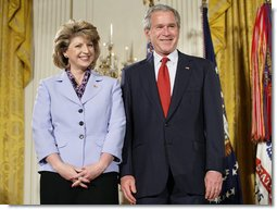President George W. Bush joins military spouse Denise Rampolla of Cheyenne, Wyo., on stage in the East Room of the White House, to receive the President's Volunteer Service Award Friday, May 11, 2007, during a commemoration of Military Spouse Day. White House photo by Eric Draper