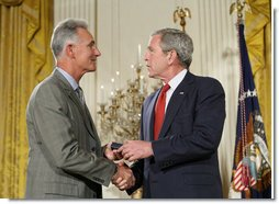 President George W. Bush congratulates military spouse Michael Winton of Wright-Patterson Air Force Base, Ohio, as Winton is presented with the President's Volunteer Service Award Thursday, May 10, 2007, in the East Room of the White House during a celebration of Military Spouse Day. White House photo by Eric Draper