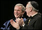 President George W. Bush, sitting with Saint Vincent College Archabbot and Chancellor Rev. Douglas Nowicki, is applauded prior to being introduced Friday, May 11, 2007, to deliver the commencement address to graduates at Saint Vincent College in Latrobe, Pa. White House photo by Joyce Boghosian