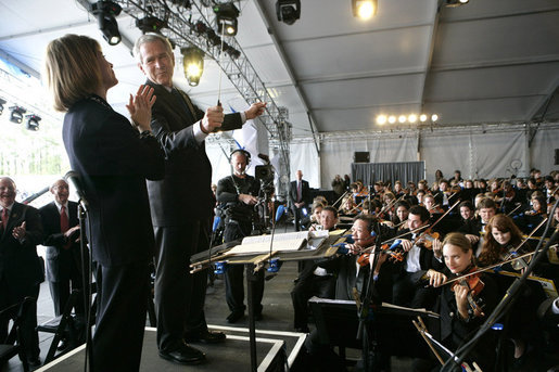 President George W. Bush looks toward conductor JoAnn Falletta as he directs the Virginia Symphony Orchestra Sunday, May 13, 2007, during the celebration marking the 400th anniversary of the Jamestown Settlement. White House photo by Eric Draper