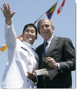 President George W. Bush holds a coin presented to him by U.S. Coast Guard graduate Daniel Kyung-Hyun Han, after President Bush presented him with his commission Wednesday, May 23, 2007, at the U.S. Coast Guard Academy commencement in New London, Conn. White House photo by Joyce Boghosian