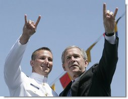 President George W. Bush and U.S. Coast Guard graduate Brian Robert Staudt offer the Texas Longhorns hand sign out to the audience following the President's address to the graduates Wednesday, May 23, 2007, at the U.S. Coast Guard Academy commencement in New London, Conn. White House photo by Joyce Boghosian
