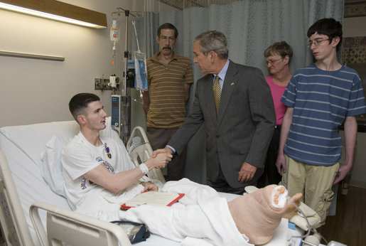 President George W. Bush shakes the hand of Cpl. Ryan T. Dion of Manchester, Conn., after awarding him a Purple Heart Thursday, May 25, 2007, during a visit to the National Naval Medical Center in Bethesda, Md., where the Marine is recovering from wounds received in Operation Iraqi Freedom. With them are Cpl. Dion's parents, Thomas and Patricia Dion, and brother, Justin. White House photo by Joyce N. Boghosian