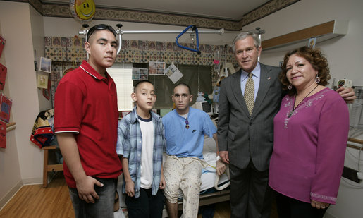 President George W. Bush stands with Cpl. Manuel Provencio of Tucson, after awarding him a Purple Heart Friday, May 25, 2007, during a visit to the National Naval Medical Center in Bethesda, Md., where the Marine is recovering from wounds received in Operation Iraqi Freedom. With them are Cpl. Provencio's mother, Manuela, and brothers, Carlos, in red, and Angel. White House photo by Joyce N. Boghosian