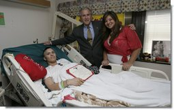 President George W. Bush stands with PFC. Arturo E. Weber and his cousin, Lisa, after awarding the Marine with a Purple Heart during a visit Friday, May 25, 2007, to the National Naval Medical Center in Bethesda, Md., where he is recovering from wounds received in Operation Iraqi Freedom.  White House photo by Joyce N. Boghosian