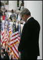 "President George W. Bush bows his head during the reading of the invocation at the Memorial Day ceremony Monday, May 28, 2007, at Arlington National Cemetery in Arlington, Va. Addressing the gathered audience President Bush said, ""The greatest memorial to our fallen troops cannot be found in the words we say or the places we gather. The more lasting tribute is all around us—a country where citizens have the right to worship as they want, to march for what they believe, and to say what they think."" White House photo by Joyce Boghosian"