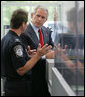President George W. Bush listens to Ty Bowers, Assistant Director of U.S. Customs and Border Protection, as he demonstrate how people are screened at primary and secondary locations Tuesday, May 29, 2007, during a tour of the Federal Law Enforcement Training Center in Glynco, Ga. White House photo by Eric Draper