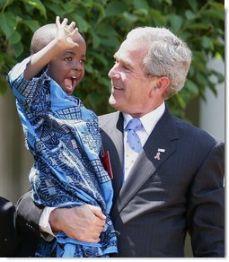 President George W. Bush holds Baron Mosima Loyiso Tantoh in the Rose Garden of the White House Wednesday, May 30, 2007, after delivering a statement on PEPFAR, the President's Emergency Plan for AIDS Relief. Baron's mother, Kunene Tantoh, representing Mothers to Mothers, an organization which provides treatment and support services for HIV-positive mothers in South Africa, joined President Bush with other guests in the Rose Garden for the statement. White House photo by Eric Draper