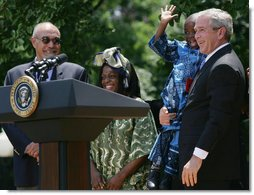 "President George W. Bush holds Baron Mosima Loyiso Tantoh in the Rose Garden of the White House Wednesday, May 30, 2007, after delivering a statement on PEPFAR, the President's Emergency Plan for AIDS Relief. With them are the boy's mother, Kunene Tantoh, representing Mothers to Mothers, which provides treatment and support services for HIV-positive mothers in South Africa, and Dr. Jean ""Bill"" Pape, internationally recognized for his work with infectious diseases.  White House photo by Chris Greenberg"