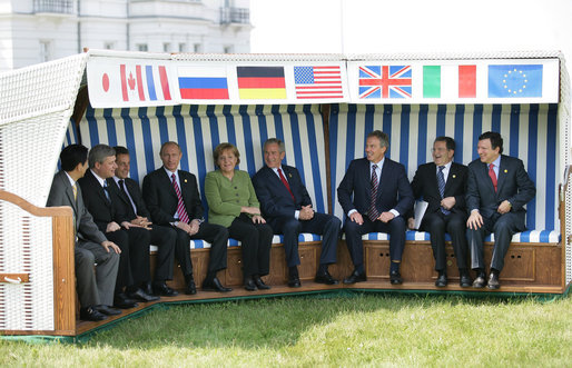 Leaders of the G8 sit on a canopied bench after meeting with Junior G8 Student Leaders Thursday, June 7, 2007, in Heiligendamm, Germany. From left, and under their respective country flags, are: Prime Minister Shinzo Abe of Japan; Prime Minister Stephen Harper of Canada; President Nicolas Sarkozy of France; Chancellor Angela Merkel of Germany, President George W. Bush of the United States; Prime Minister Tony Blair of the United Kingdom; Prime Minister Romano Prodi of Italy, and Jose Manuel Barroso, President of the European Commission. White House photo by Eric Draper