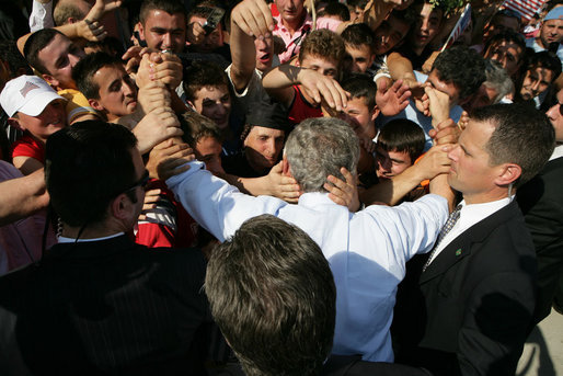 President George W. Bush is covered with the hands of Albanians has he's greeted with an outpouring of welcome Sunday, June 10, 2007, during a stop in Fushe Kruje. The stop marked the first time a sitting U.S. president has visited the country. White House photo by Eric Draper