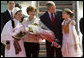 Mrs. Laura Bush holds flowers presented to her by Sara Shehu, 12, and Frensis Spaho, 13, upon the arrival Sunday, June 10, 2007, of she and President George W. Bush to Albania. The visit marked the first by a sitting U.S. president to the country. White House photo by Chris Greenberg