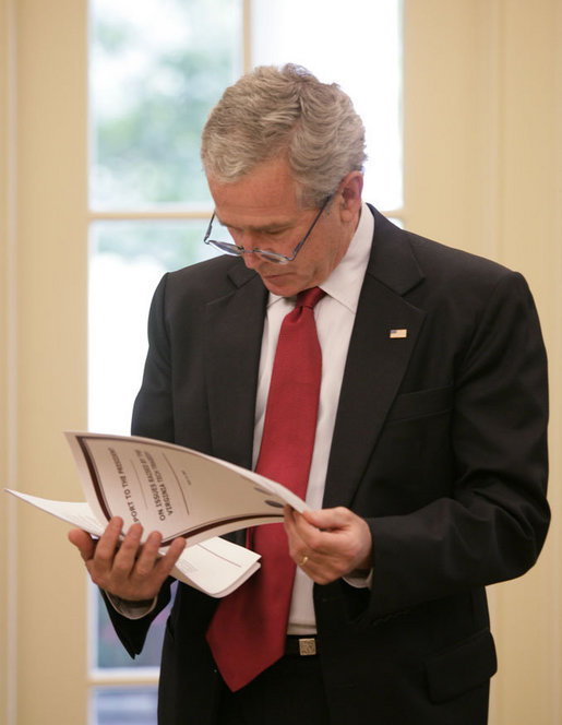 President George W. Bush reads the Report to the President on Issues Raised by the Virginia Tech Tragedy in the Oval Office Wednesday, June 13, 2007. The report, presented to President Bush Wednesday afternoon, was compiled by the departments of Justice, Health and Human Services and Education in response to the tragic shooting rampage at Virginia Tech April 16, 2007 in Blacksburg, Va. White House photo by Eric Draper