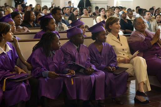 "Mrs. Laura Bush sits with sixth-grade of the Elsie Whitlow Stokes Community Freedom Public Charter School graduates during ceremony marking their accomplishment Friday, June 15, 2007, at All Souls Unitarian Church in Washington, D.C. ""Keep caring for the community,"" said Mrs. Bush in her commencement address. ""Be good stewards of our environment, as you were when you helped clean up the Potomac River at Hard Bargain Farm."" White House photo by Shealah Craighead"